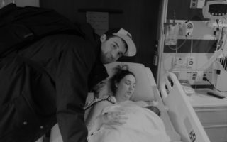 A man leans over his wife, who is is lying in a hospital bed with her their new baby.