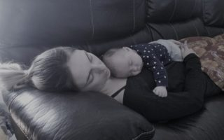 A mother sleeps on the couch with her baby, also sleeping, on her chest.