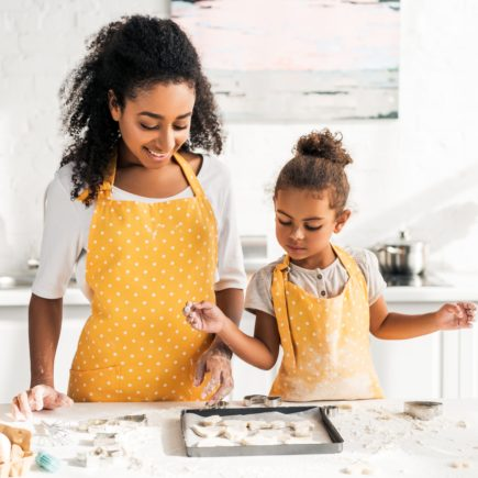 A mother and daughter wear matching aprons while baking cookies.