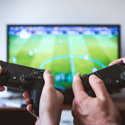 Two pairs of hands are holding PS4 controllers in front of a TV.