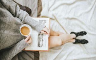 A woman is reading a book and holing a cup of coffee.