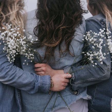Three woman have their backs to the camera, and are embracing each other with flowers in their hands.