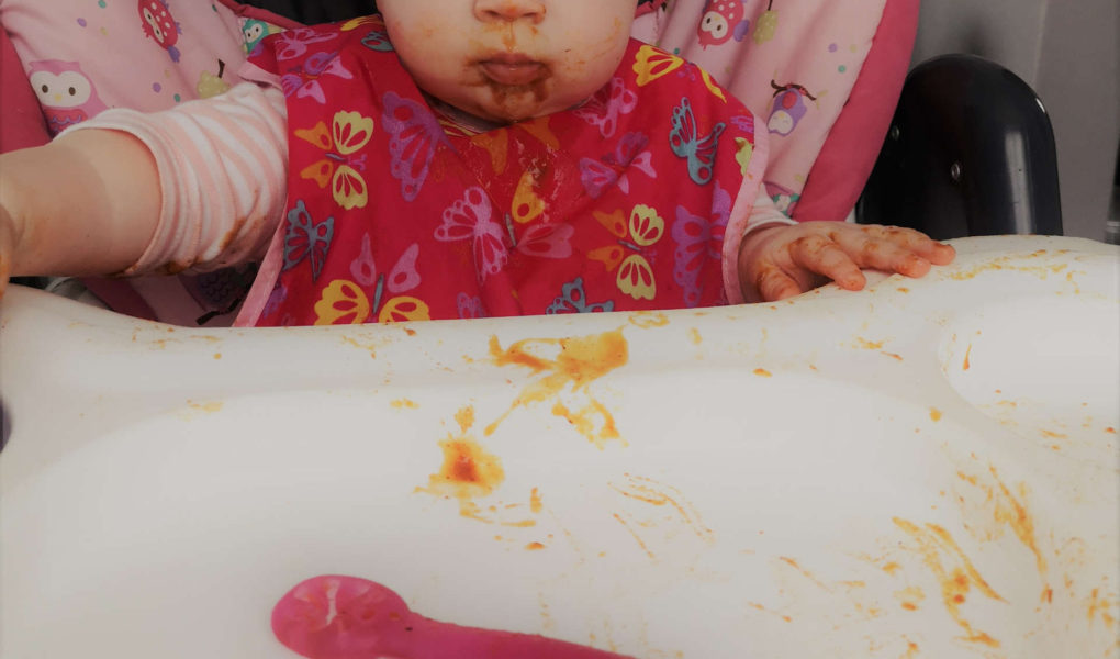 A baby is sitting in a high chair with food all over her face.