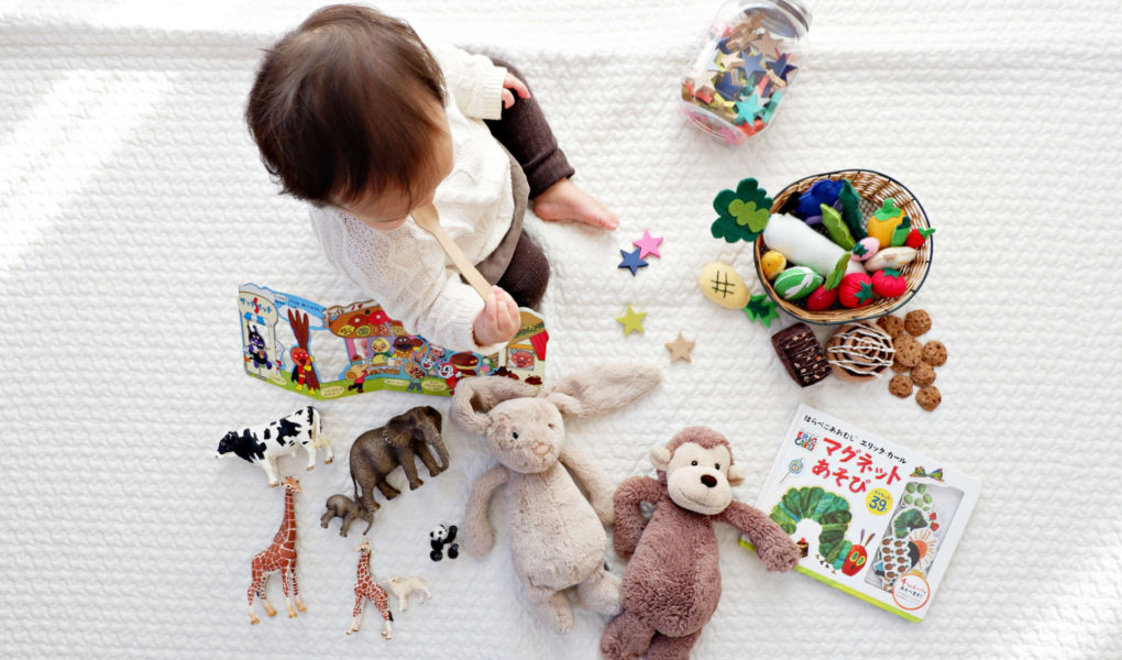 A baby is sitting on the floor surrounded by toys.
