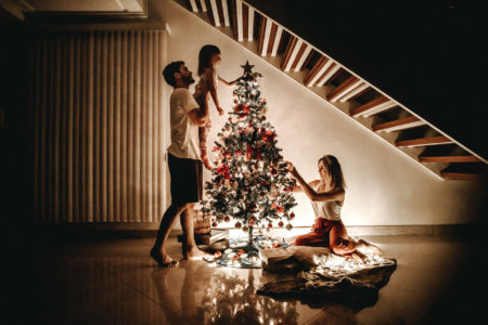 A small family is decorating a Christmas tree. Mom is on the ground and Dad is lifting the child.