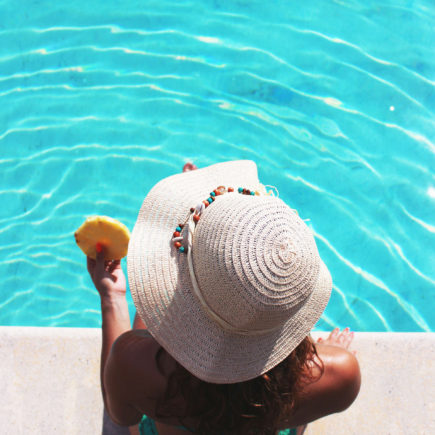 A Woman is sitting on the edge of a pool, eating a piece of pineapple.