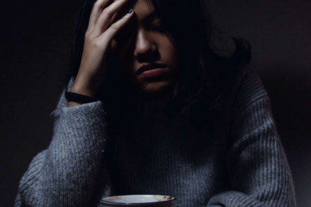 Woman looking stressed over a coffe cup