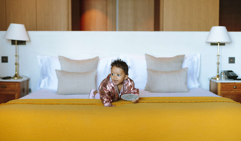 Baby crawling on a yellow bed.